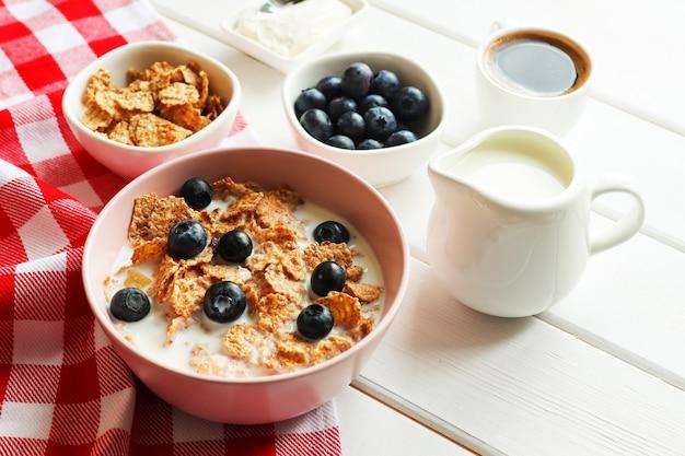 ミルクブルーベリーと木製のテーブルの上のコーヒーのクローズアップと全粒粉フレークのおいしい朝食
