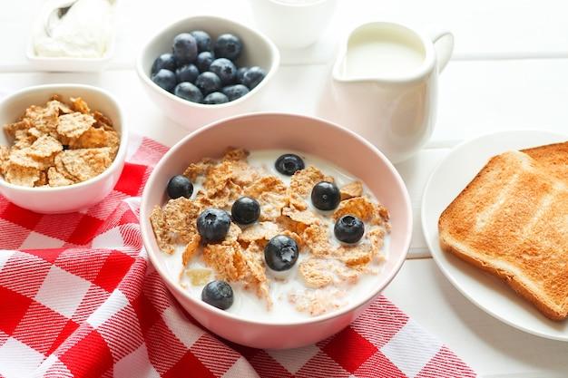 ミルクブルーベリーとトーストと全粒粉フレークのおいしい朝食木製テーブルのクローズアップダイエットと健康食品の概念