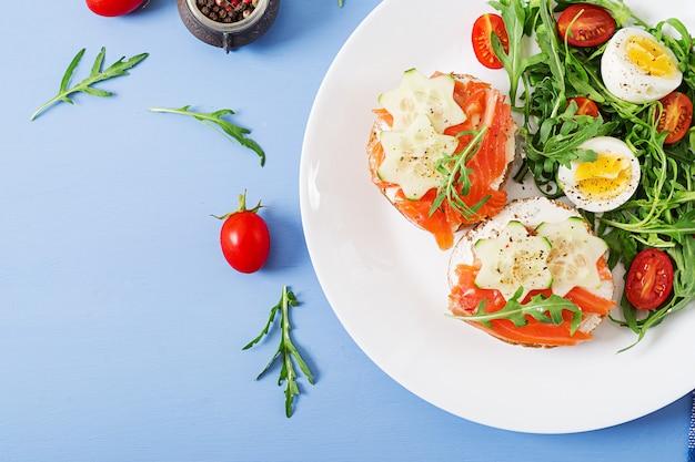 Вкусный завтрак. открытые бутерброды с лососем, сливочным сыром и ржаным хлебом в белой тарелке и салат с помидорами, яйцом и рукколой. вид сверху. плоская планировка