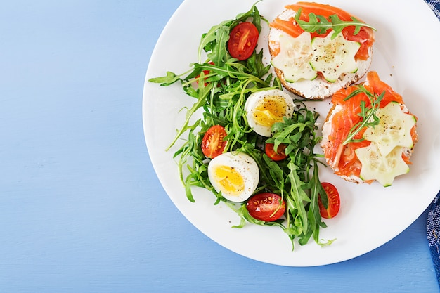 Tasty breakfast. open sandwiches with salmon, cream cheese and rye bread in a white plate and salad with tomato, egg and arugula. top view. flat lay