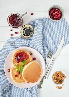 Вкусный завтрак. блин на тарелку и банку с соусом, клюквой и орехами. тарелка на салфетке на столе.