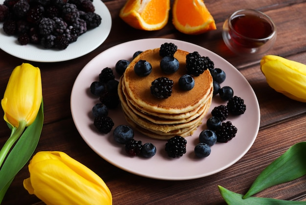 素朴な木製のテーブルにブルーベリーとブラックベリーのクローズアップとおいしい朝食パンケーキ Premium写真