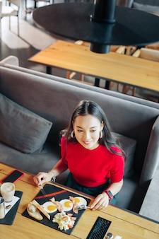 おいしい朝食。レストランでおいしい朝食を食べている魅力的な若い黒髪の女性のトップ ビュー
