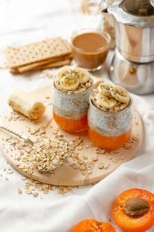 Tasty breakfast with coffee, chia seed pudding with banana, smashed fresh apricot and oat meals on wooden board. vertical