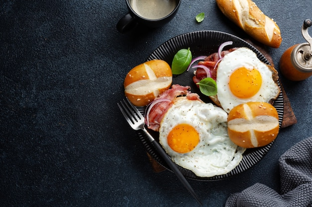 Tasty breakfast with eggs, bacon and bread served on plate on dark background.