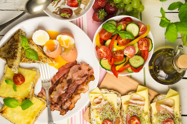 Tasty breakfast with eggs and bacon, sandwiches, on the table view from above