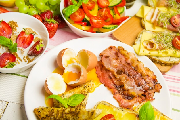 Tasty breakfast with eggs and bacon, sandwiches, on the table