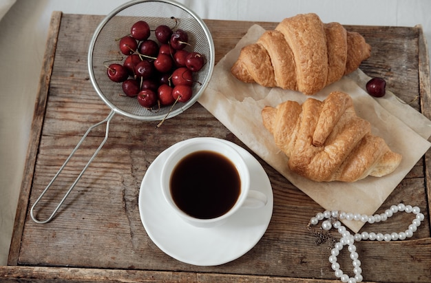 Tasty breakfast with fresh croissant, coffee, cherries on a wooden tray. espresso on a breakfast tray. breakfast pearl necklace