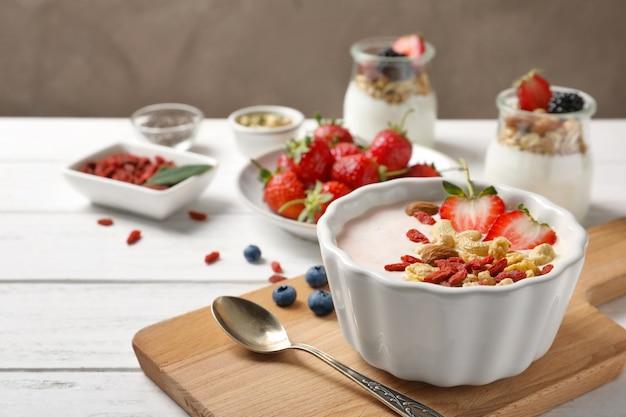 Tasty breakfast with goji berries in dish on wooden board