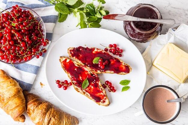 赤スグリのマーマレードクロワッサンバターとミントの葉を使ったおいしい朝食。