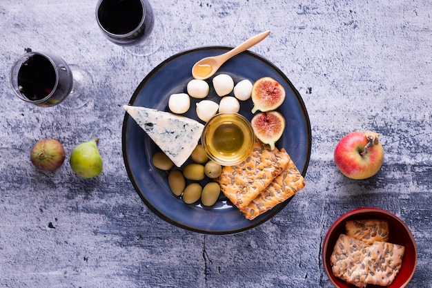 Tasty brie cheese and snacks on a table