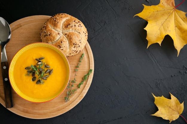 黒の背景に、チーズと種、ハーブ、パンを添えたおいしい明るい自家製カボチャスープ
