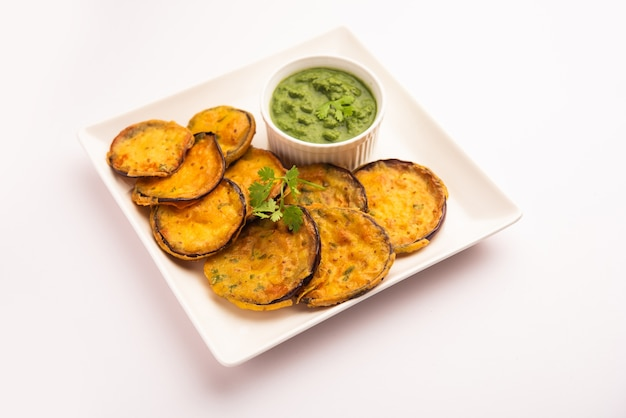Tasty brinjal pakora or crispy eggplant fritters, indian tea time snack served with green chutney