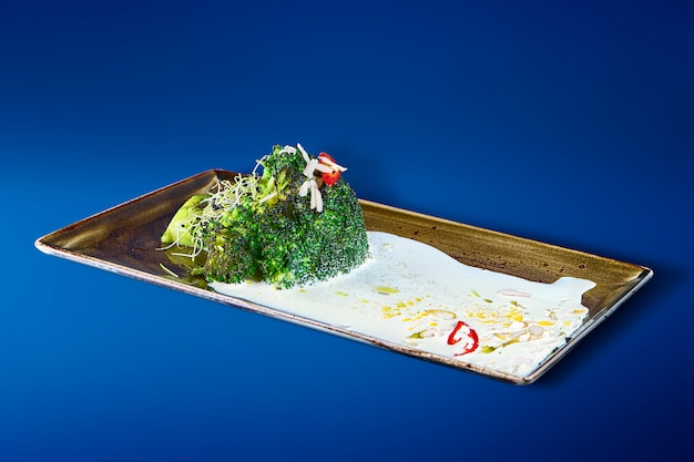 Tasty broccoli with yogurt sauce, hot pepper and spices on a stylish black plate. restaurant serving food. vegetarian food. close up..