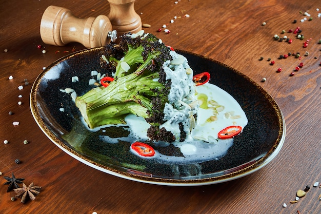 Tasty broccoli with yogurt sauce, hot pepper and spices on a stylish black plate. restaurant serving food. vegetarian food.. wooden table.