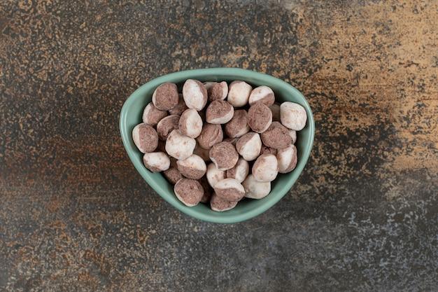 Tasty brown candies in blue bowl.
