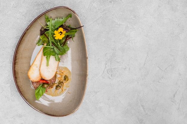 Tasty bruschetta and herbs top view