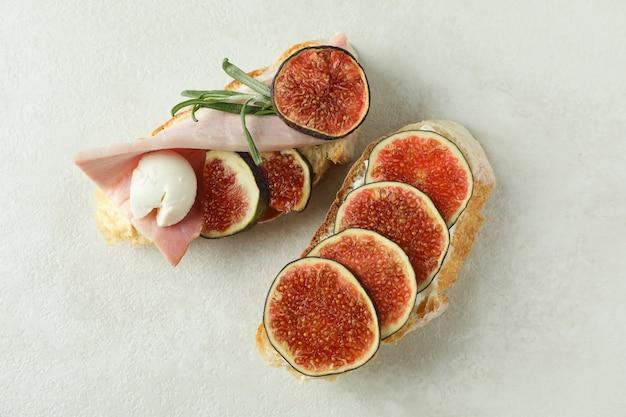Вкусная брускетта с инжиром на белом текстурированном фоне