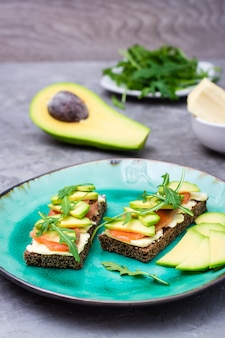 Tasty bruschetta with salmon, butter, avocado and arugula on a plate