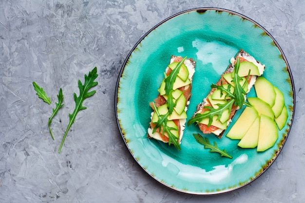 Tasty bruschetta with salmon, butter, avocado and arugula on a plate.