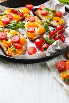 テーブルの上に、鍋にトマトが入ったおいしいブルスケッタ