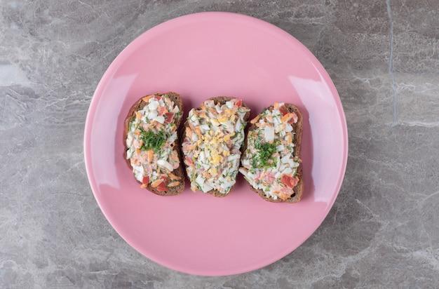 Вкусная брускетта с овощами на розовой тарелке.