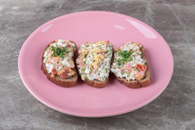 Bruschetta saporita con le verdure sul piatto rosa.