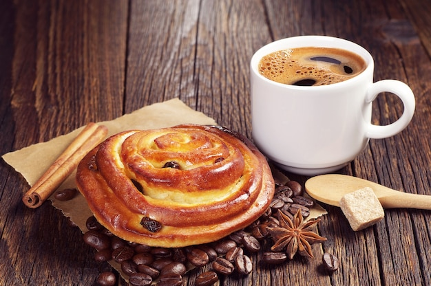 Tasty bun with raisins and cup of hot coffee on vintage wooden table