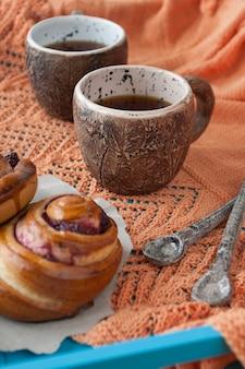 ジャムと青い木のお茶2杯のおいしいパン。次に、2つのスプーンと明るいオレンジのニットチェック柄があります。