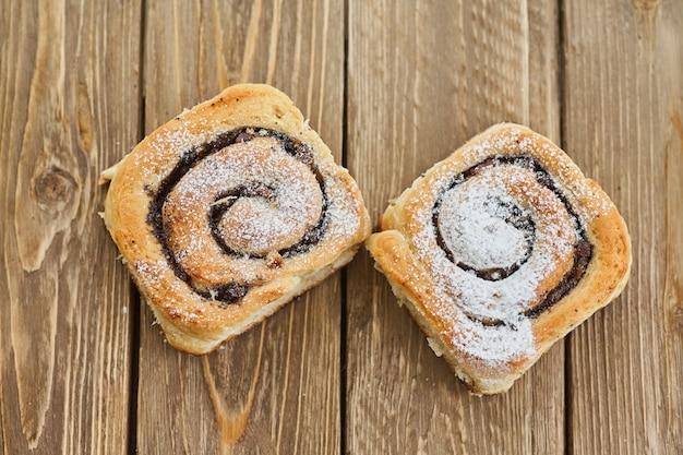 Вкусные булочки с изюмом на коричневый деревенский деревянный столик. свежая выпечка. завтрак. хлеб. вид сверху