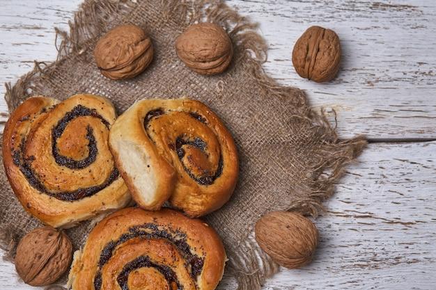 白い素朴な木製のテーブルにレーズンとおいしいパン。焼きたてのパン屋。朝ごはん。パン。上面図