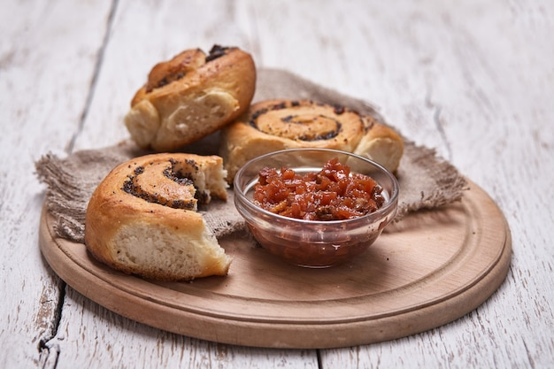 Вкусные булочки с изюмом на белый деревенский деревянный столик. свежая выпечка. завтрак. хлеб. вид сверху