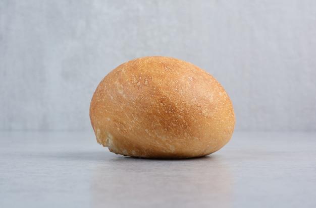 Вкусная булочка для гамбургера на мраморном фоне. фото высокого качества
