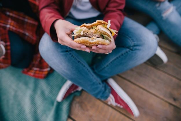 女性の手においしいハンバーガー。テイクアウトのジャンクフードの上面図。不健康な食事と急いで食べる、友情と一緒に時間を共有するコンセプト