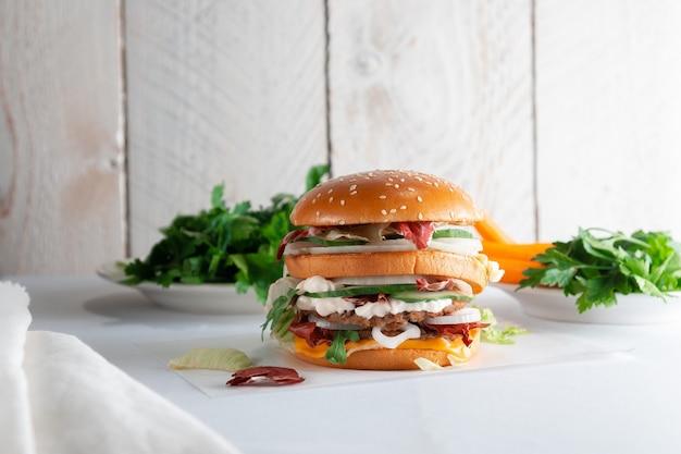 Вкусный бургер на светлом деревянном столе