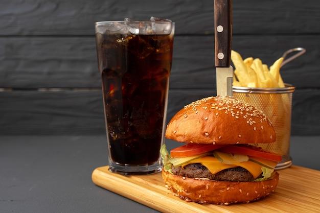 검은 나무 바탕에 맛있는 햄버거를 닫습니다.