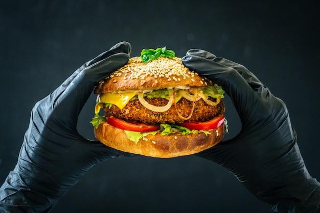 Вкусный бутерброд с гамбургером в руках в черных перчатках