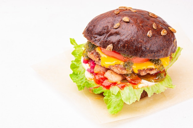 Tasty burger with bacon and sunflower seeds isolated on white.