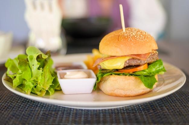 Вкусный бургер с говядиной подается на тарелке с соусами и салатом