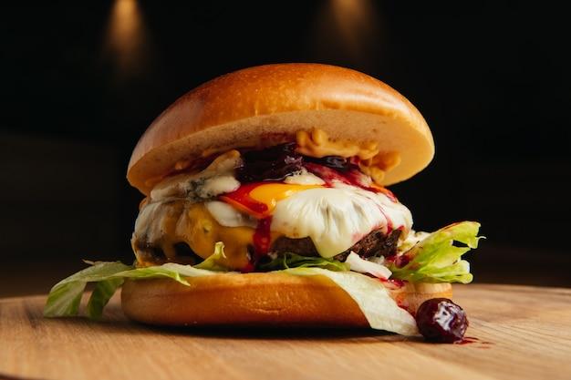 チェリージャム、肉、グリーンサラダをボードに乗せたおいしいハンバーガー