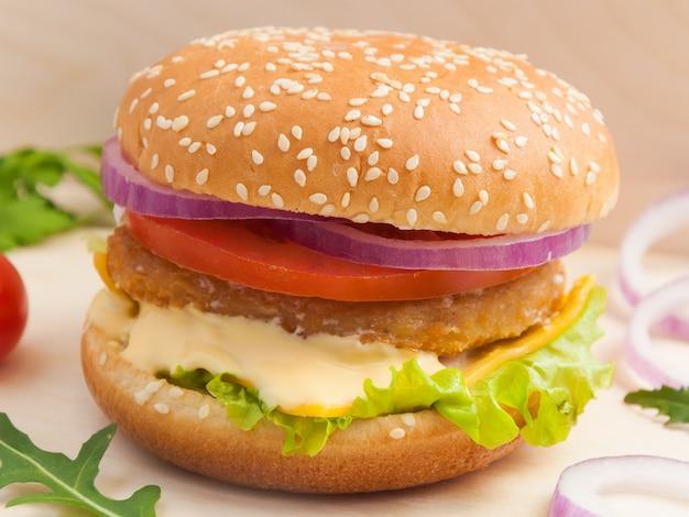Вкусный бургер с куриной котлетой на деревянной доске