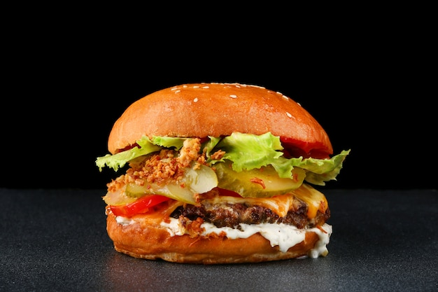 Tasty burger with chicken on dark isolated background. homemade hamburger with fresh vegetables, cheese