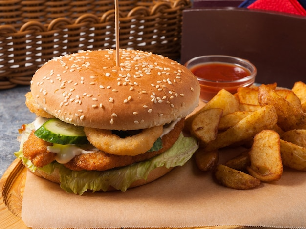 Tasty burger with chicken fillet with potato slices and tomato sauce