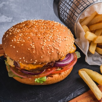Tasty burger with chicken, red onion cheese, lettuce and french fries