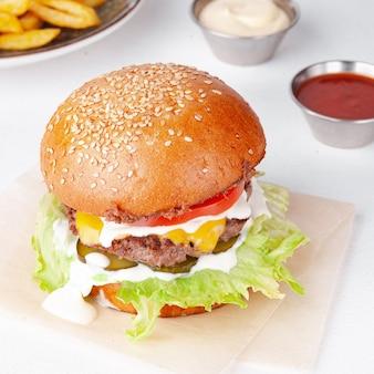 감자 튀김, 화이트 소스와 케첩 흰색 배경에 고립 된 맛있는 햄버거. 개념 : 메뉴 사진.