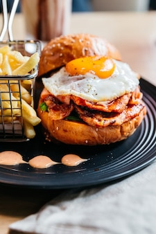 Tasty burger with fried egg served with fries in black plate on wooden table.