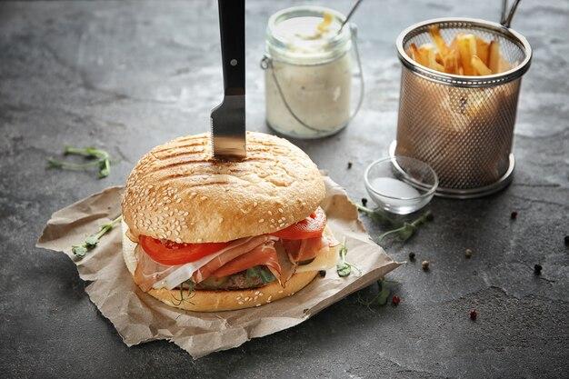 Вкусный бургер с прошутто на столе