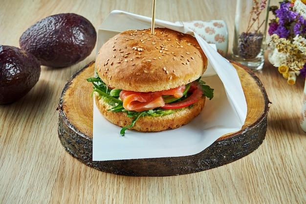 サーモン、トマト、ルッコラ、キュウリ、木製のテーブルで木の板においしいハンバーガー。フィッシュバーガー。健康的なスナック。クローズアップビュー