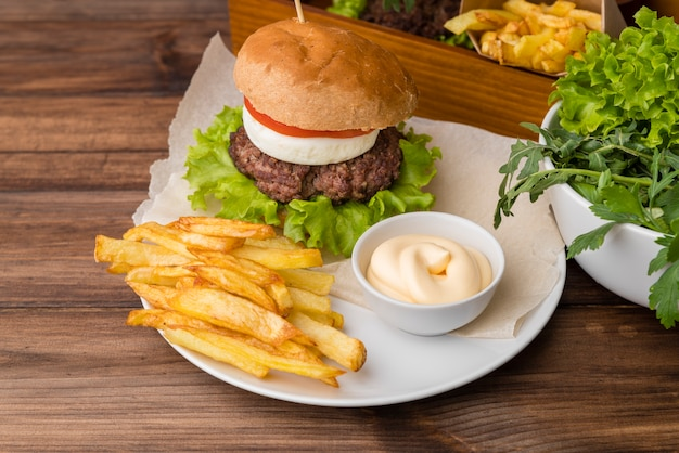 Tasty burger with sauce and french fries