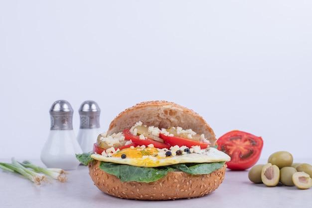 Вкусный гамбургер с помидорами, сыром, листьями салата на белом.